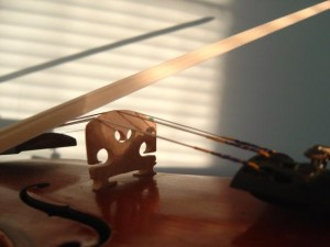 Closeup photo of a violin with a bow in a sunbeam