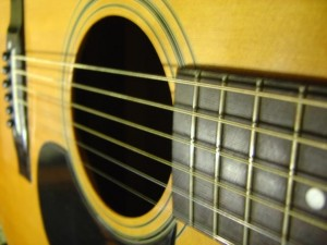 close up photo of acoustic guitar with fingerboard sound hole strings and pick guard