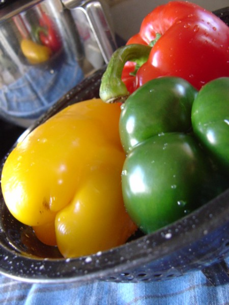 three bell peppers with reflection in silver bowl