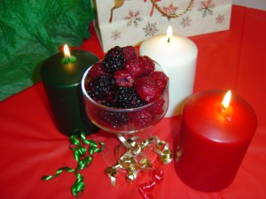 photo of dish of raspberries and blackberries with Christmas holiday candles and ribbons