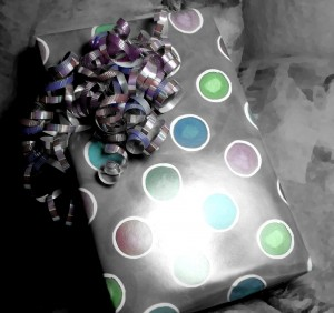black and white colorized photo of a wrapped birthday present with curly ribbon