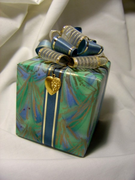 photo of blue and green wrapped package with bow and heart pendant