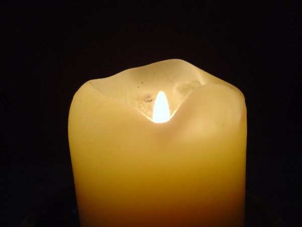 photo of cream colored candle with burning lit flame in dark