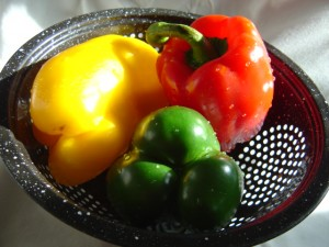 photo of a kitchen collander with three red yellow and green bell peppers