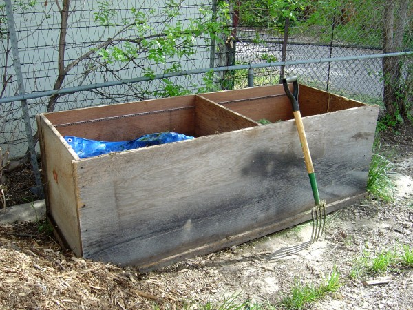 photo of a two compartment compost bin with a pitchfork leaning up against it