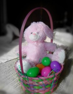 colorized photo of stuffed bunny in an easter basket with colorful eggs