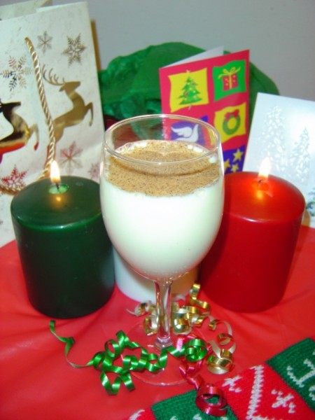 photo of egg nog with christmas candles ribbons and holiday decor