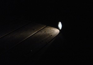 photo of flashlight shining on deck boards in darkness of night
