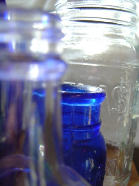 photo of clear and cobalt blue glass bottles and jars