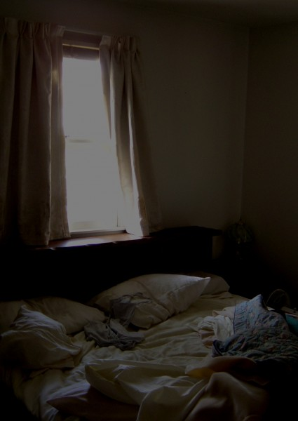 photo of messy bed with sunlight streaming through window