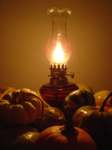 photo of burning oil lamp surrounded by various fall squash and gourds