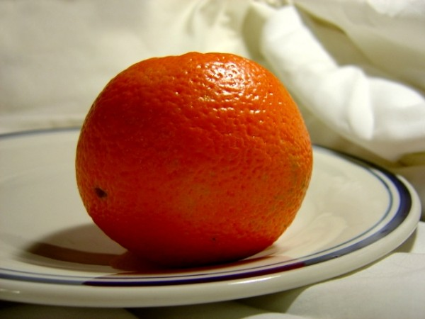 photo of an orange on a plate