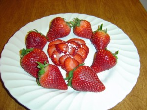 photo of strawberries arranged on a plate with a heart shape