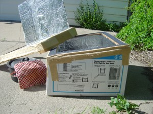 photo of home made solar box cooker with pot of food next to it