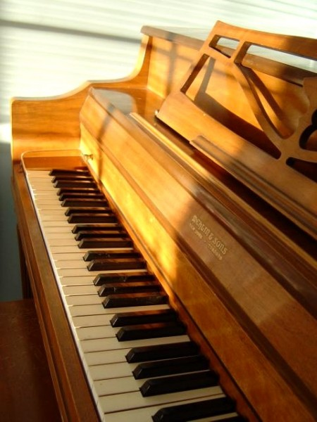 photo of a golden brown spinet upright piano with a sunbeam