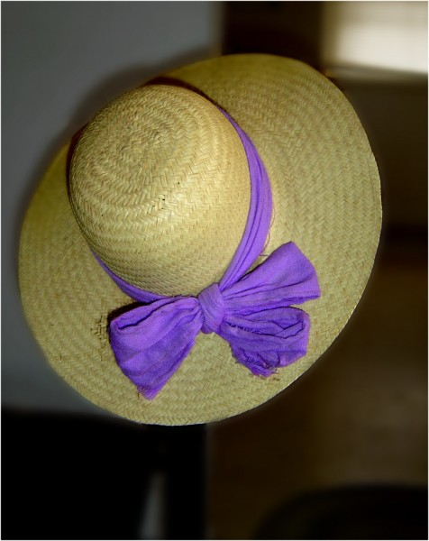 Photo of straw hat hanging on edge of a chair