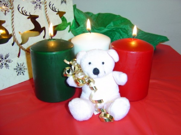 Photo of white teddy bear with burning Christmas candles