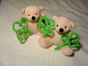Photo of Two white teddy bears holding shamrocks
