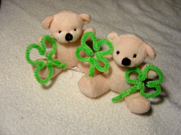 Photo of Two white teddy bears holding shamrocks