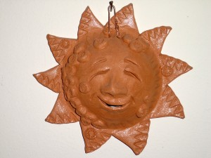 Photo of a terra cotta ornament of a smiling sun