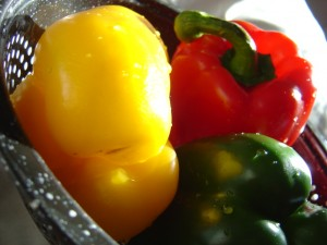 closeup photo of three red yellow and green bell peppers