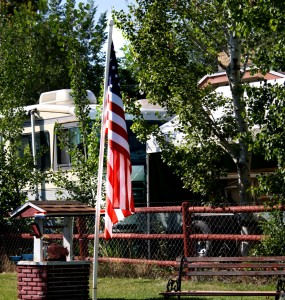 Free photograph of an American Flag on a flagpole next to a garden well and bench