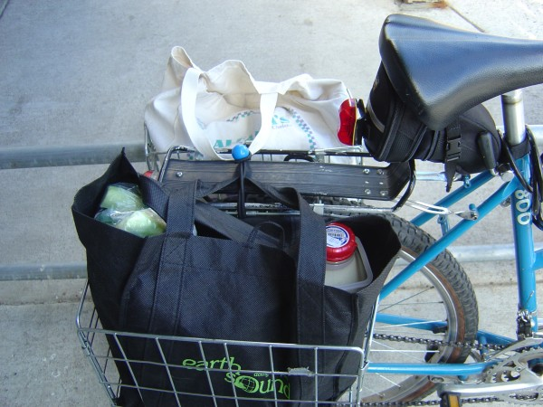 photo of rear bicycle baskets full of bags of groceries