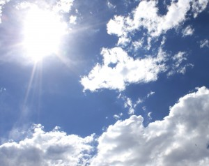 free photograph of the sun shining in a beautiful blue sky with white clouds