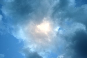 This free photo features the sun shining through clouds in a blue sky