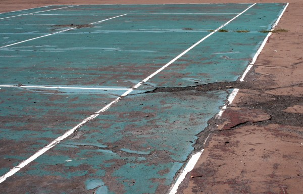 Free photo of a tennis court with badly damaged asphalt