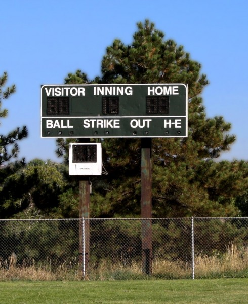 Free photo of a baseball scoreboard with pine trees in the background