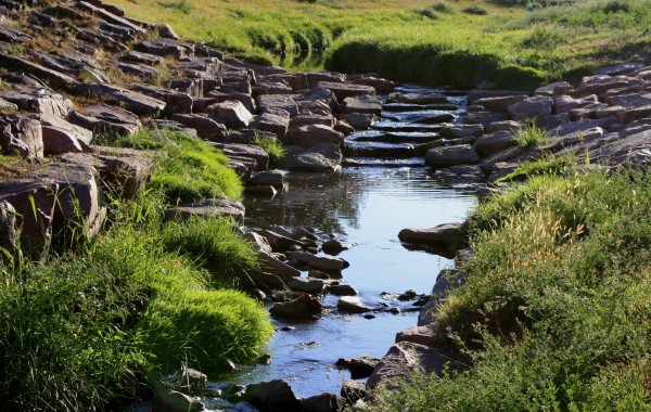 Free photo of a small stream flowing over a small rock waterfall