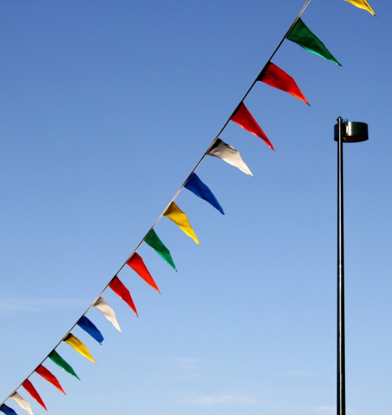 Free photo of a street lamp with pennant flags flying in the wind