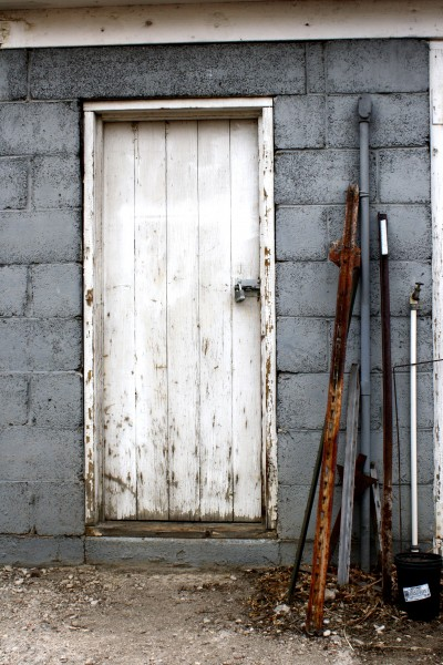 Old Shed Door With Metal Stakes Leaning Next To It Picture