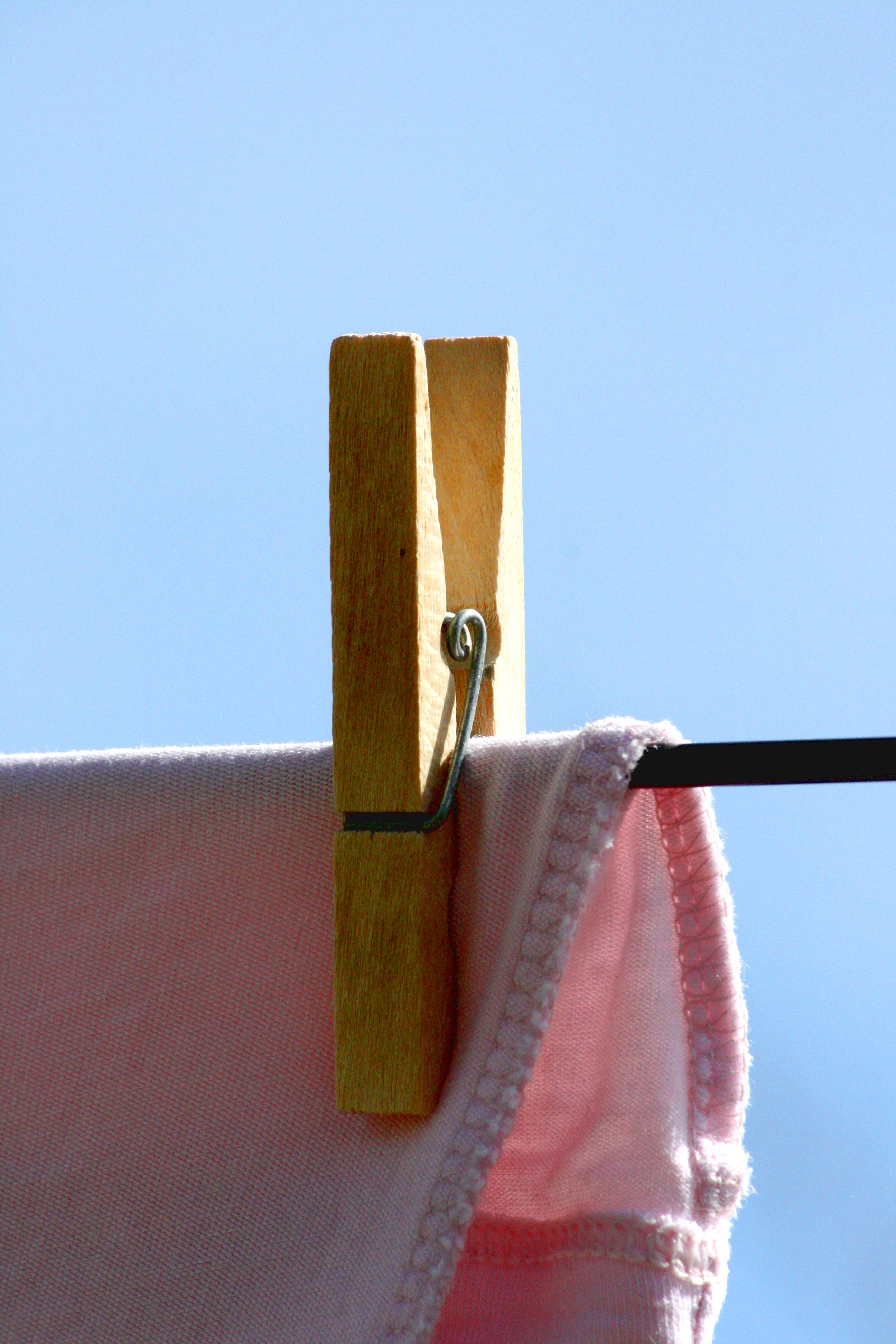 Wooden Clothespin Holding Drying Laundry On Clothesline