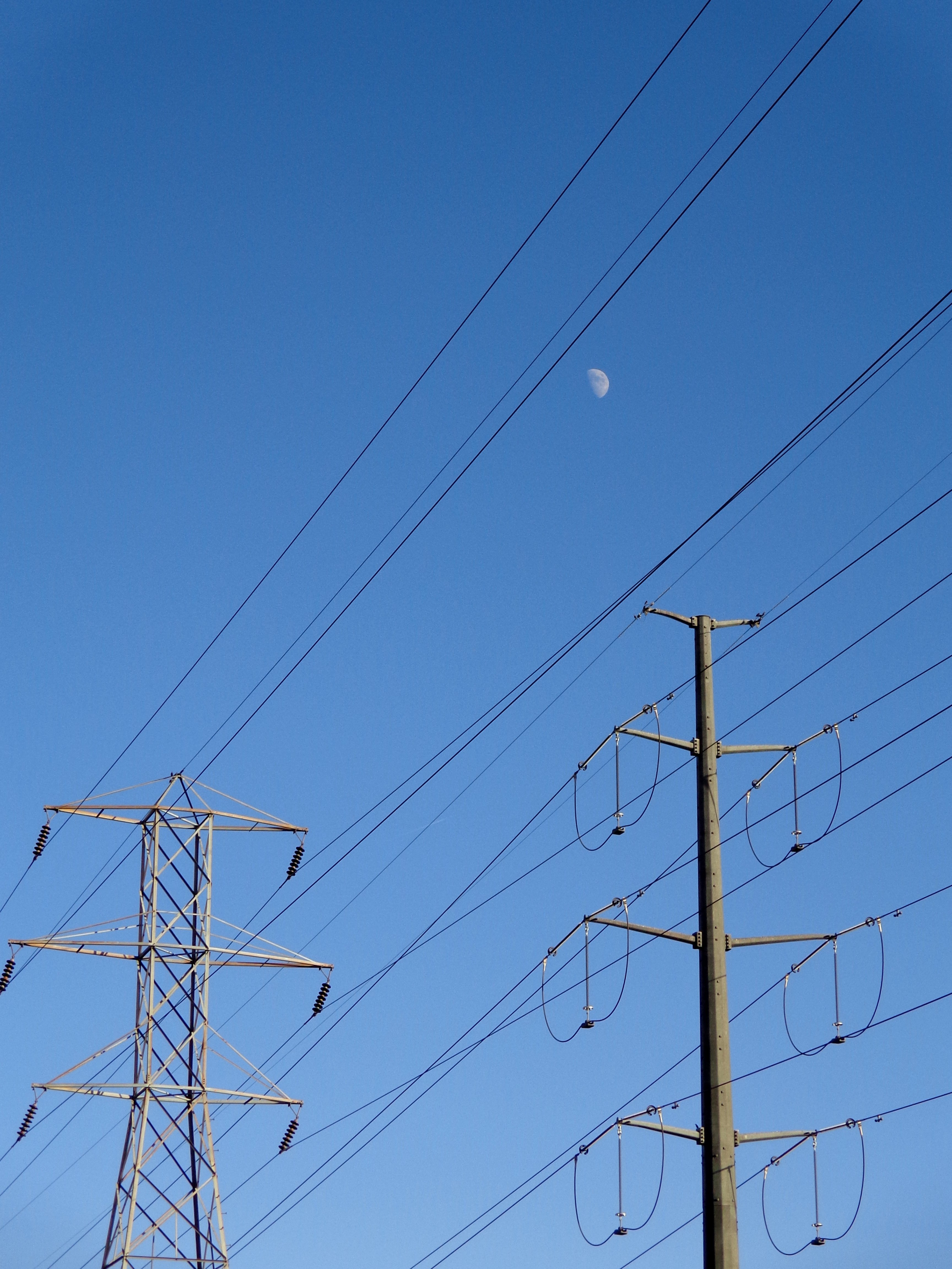Electric Power Lines : Electric power lines with blue sky and daytime moon