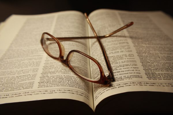 Reading Glasses atop Pages of Open Dictionary Book - Free High Resolution Photo