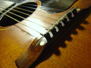 closeup photo of acoustic guitar bridge, sound hole with strings and pegs