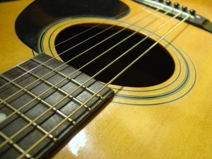 photo of an acoustic guitar sound hole with strings and pick guard