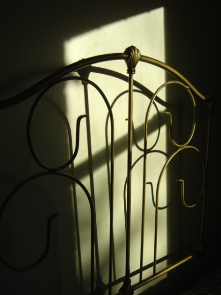 photo of antique bed headboard with shadows in sunbeam