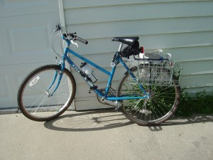 photo of blue bicycle with rear bike baskets