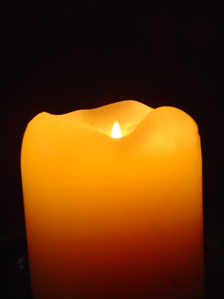 photo of orange candle with flame burning in the darkness