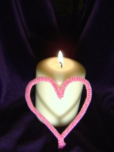 photo of burning lit candle with flame and pink heart