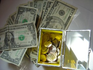 photo of a variety of dollar bills with a glass box full of coins