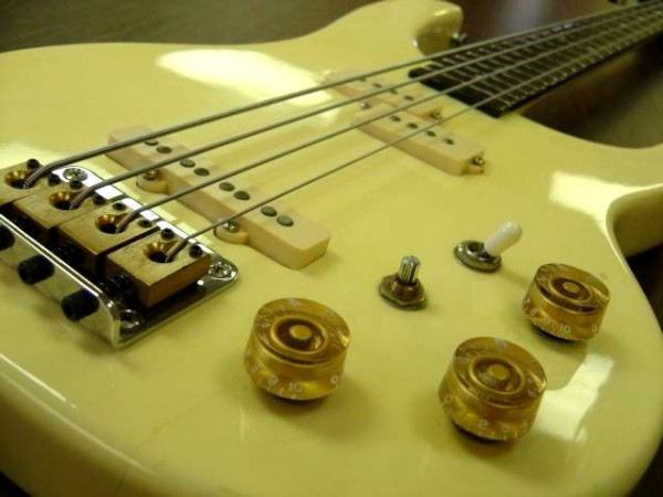 photo of electric bass guitar with strings and knobs