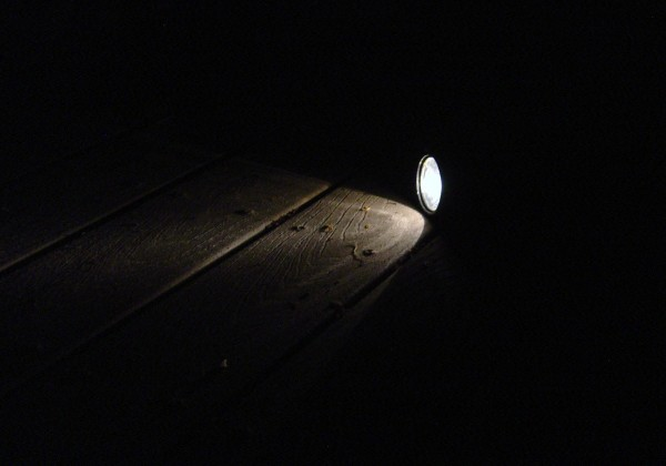 photo of flashlight shining on deck boards in darkness of night