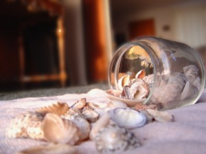 Sea shells spilling out of glass jar