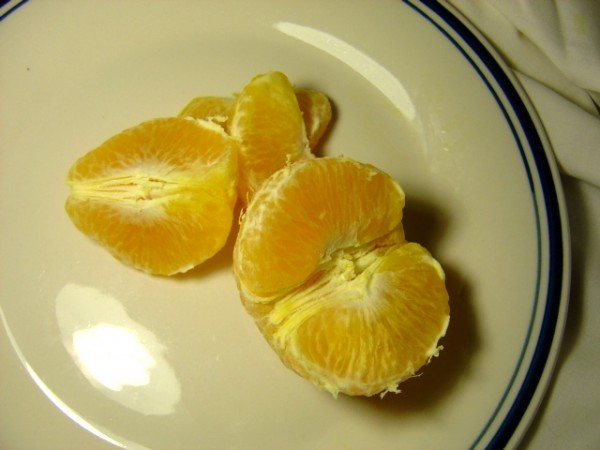 Photo of peeled orange and orange sections on a plate
