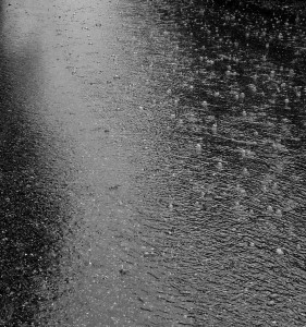 photo of raindrops falling on wet pavement with ripples and bubbles