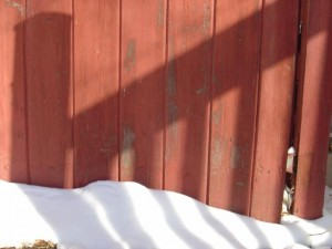 photo of a shadow of deck railing on a red wooden fence with snow
